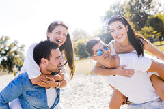 Group of young happy people carrying women on a sandy beach Stock Photography