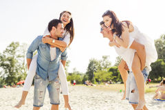 Group of young happy people carrying women on a sandy beach Royalty Free Stock Image