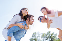 Group of young happy people carrying women on a sandy beach Royalty Free Stock Photography