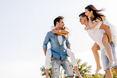 Group of young happy people carrying women on a sandy beach Royalty Free Stock Photo