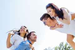 Group of young happy people carrying women on a sandy beach Stock Photos
