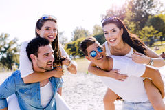 Group of young happy people carrying women on a sandy beach Stock Images