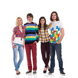 Group of a young happy people. Four young students standing together and smiling. Full length studio shot isolated on white Royalty Free Stock Images