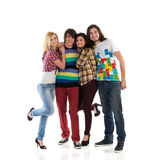Group of a young happy people. Four young students standing together and smiling. Full length studio shot  on white Royalty Free Stock Photography