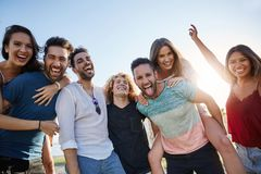 Group of young happy people standing together outside stock image