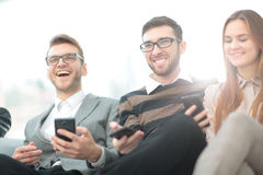 A group of young and happy young people using their phones and c Royalty Free Stock Photo
