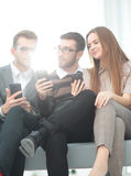 A group of young and happy young people using their phones and c Stock Photos