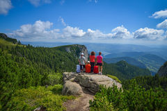 Group of young hikers sitting on a cliff edge in the Ceahlau mountains in Romania Stock Image