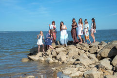 Group of young hippie womens standing together at a beach on a summer day. Happy young people enjoying a day at beach. Royalty Free Stock Image