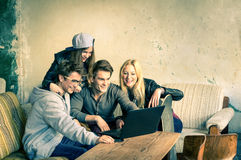 Group of young hipster best friends with computer laptop. In urban alternative location - Concept of friendship and fun with new trends and technology Royalty Free Stock Photo