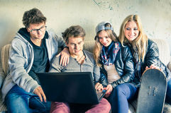 Group of young hipster best friends with computer. In urban alternative studio - Concept of friendship and fun with new trends and technology Royalty Free Stock Photos