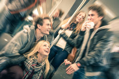 Group of young hipster friends having fun and talking. Group of young hipster friends having fun interaction and talking in subway train - Vintage filtered look Stock Photography