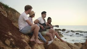 Group of young hipster friends sitting on the rocks by the seashore and playing guitar and singing songs. Slowmotion. Shot stock video footage