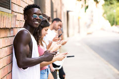 Group of young hipster friends using smart phone in an urban area. Royalty Free Stock Photos