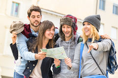 Group of young hipster tourists friends cheering with city map Royalty Free Stock Images
