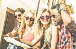 Group of young hipster tourists friends having fun at city tour on travel trip. Group of young hipster tourists friends cheering with city map in the old town Royalty Free Stock Photography