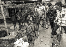 Group of young Indian men and children. A group of young men share a joke watched by young children in a rural village in India. Poverty and illiteracy are rife Royalty Free Stock Images