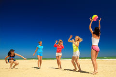Group of young joyful girls playing volleyball Stock Images