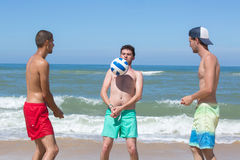 Group young joyful men playing volleyball on beach Stock Photo