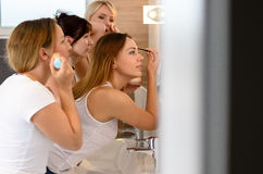 Group of young ladies applying their makeup. Together in a long mirror as they freshen up midday with focus to the profile Stock Images