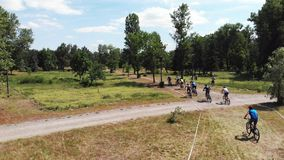 Group of young male cyclists are chasing leader at mountain bike race in Muromets Park.  stock video footage