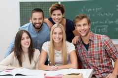 Group of young male and female students. Happy diverse group of young male and female students posing together behind a desk in the classroom smiling cheerfully Royalty Free Stock Photo