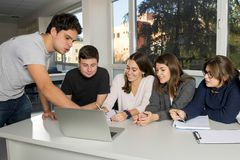 Group of young male and female teenager university students at school sitting on classroom learning and working on project togethe stock photos