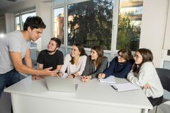 Group of young male and female teenager university students at school sitting on classroom learning and working on project togethe stock images