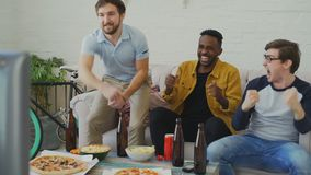 Group of young male friends watching sports match on TV together while drinking beer and eating snacks at home. Indoors stock footage