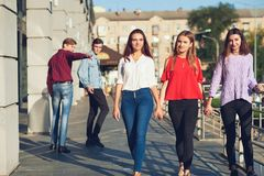 Group of young man flirting with woman in city. Stock Image