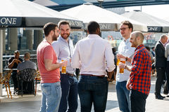 Group of young men drinking at a dockside bar royalty free stock images