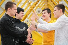 Group of young men make piramid from hands Royalty Free Stock Photo