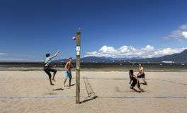Group of Young Men Playing Volleyball on Vancouver Kits Beach royalty free stock photo