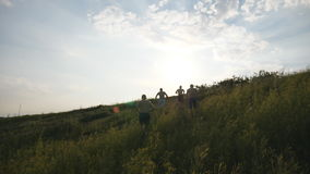 Group of young men running up the green hill over blue sky with sun flare at background. Male athletes is jogging in. Nature at sunset. Sport runners going stock video