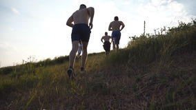 Group of young men running up the green hill over blue sky with sun flare at background. Male athletes is jogging in. Nature at sunset. Sport runners going stock footage
