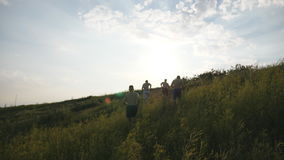 Group of young men running up the green hill over blue sky with sun flare at background. Male athletes is jogging in stock image