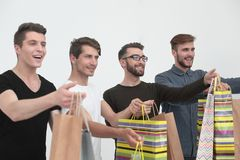 Group of young men with shopping bags. The concept of shopping stock photography