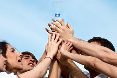 Group of young men stretching hands to a bottle Stock Photo