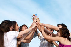 Group of young men stretching hands to a bottle. With water Royalty Free Stock Image