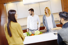 Group of young men and women cooking together at home in modern Royalty Free Stock Photography