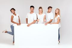 Group of smiling people with empty white board. royalty free stock photo