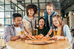 Group of young multiethnic friends having pizza stock images