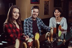Group of young multiracial smiling people resting in the pub. stock photos