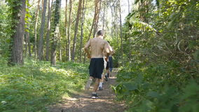Group of young muscular athletes running at the forest path. Active strong men training outdoors. Fit handsome athletic. Male sportsmens working out. People stock video
