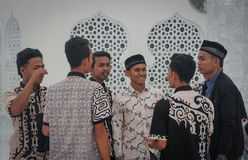 A group of young Muslim Asian men in beautiful shirts are standing near the walls of the mosque stock photo