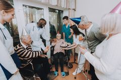 Group Young and Old People Congratulate Woman. Birthday in Nursing Home. Elderly Female Very Surprised. Woman Very Happy. Guests Hold Glasses of Drinks. Nurse stock photography