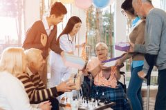 A group of young and old people in a nursing home congratulate an elderly woman on her birthday. A group of young and old people in a nursing home congratulate royalty free stock photos