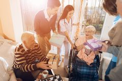 A group of young and old people in a nursing home congratulate an elderly woman on her birthday. A group of young and old people in a nursing home congratulate stock image