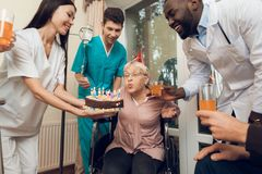 A group of young and old people in a nursing home congratulate an elderly woman on her birthday. A group of young and old people in a nursing home congratulate royalty free stock image