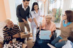 A group of young and old people in a retirement home give an elderly woman a mobile phone. A group of young and old people in a nursing home congratulate an royalty free stock image
